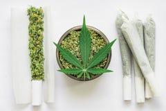 Sarclez la feuille du cannabis, du joint et d'une broyeur avec écrasé, des bourgeons de marijuana, sur une vue supérieure de fond image stock