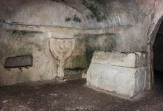 Sarcophagus and bas-relief of Menorah on the wall in the inner room of the necropolis in the Bet She`arim National Park. Kiriyat T. Ivon city in Israel Stock Image