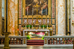 The sarcophagus of the crypt with the tomb of the Catholic saint, surrounded by icons, sculptures and candles in church of San Gio Stock Photography