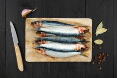Sardinas, cuchillo de cocina y condimento frescos crudos Foto de archivo libre de regalías