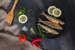 Sardine della frittura arrosto, broi, pesce della griglia sulla padella della ghisa con le verdure e spezie intorno Fotografia Stock