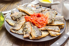 Sardine fillets fried with tomato sauce. On wood Stock Photo