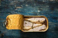 Sardines in the can on blue wooden table Royalty Free Stock Photos
