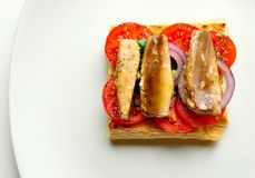 Sardines sandwich with tomato on a white background Royalty Free Stock Photo