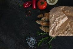 Sardinhas da fritada assado, broi, peixes da grade empacotados no papel com vegetais e especiarias ao redor Foto de Stock Royalty Free