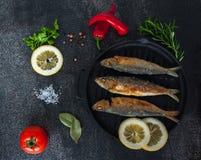 Sardinhas da fritada assado, broi, peixes da grade na frigideira do ferro fundido com vegetais e especiarias ao redor Fotos de Stock