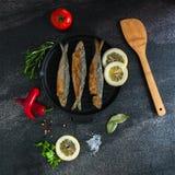 Sardinhas da fritada assado, broi, peixes da grade na frigideira do ferro fundido com vegetais e especiarias ao redor Fotografia de Stock