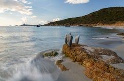 Sardinia Italien - stenar på stranden på solnedgången i den Sardinia ön Royaltyfri Bild