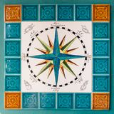 Rose of the winds and cardinal points painted on tiles in a sail. Sardinia, Italy - August 17, 2017: Rose of the winds and cardinal points painted on tiles in a Stock Photo
