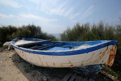 Old wooden boat abandoned on the shore royalty free stock photo