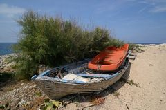 Old wooden and plastic boats abandoned on the shore royalty free stock photography