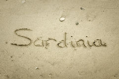 Sardinia - written in sand on beach texture Stock Photos