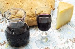 Sardinian products. Glass of red wine and slice of pecorino sardo cheese, on the table Stock Image