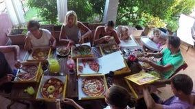Sardinige, Italië - 22/07/2017: Familiezitting bij lijst die pizza eten stock video