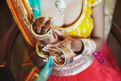 Saree indiano do desgaste da noiva que põe a pulseira dos braceletes disponível com mehndi, close-up foto de stock royalty free