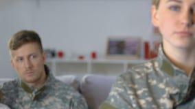Sargento fêmea que olha in camera, marido militar com o sofá de assento da filha vídeos de arquivo