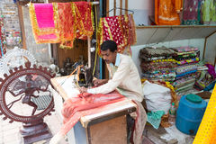 Sari craftman. New Delhi, India - October 6 2013: An Indian craftman works on a sari, a traditional cloth for women, in front of the shop in the streets of New Royalty Free Stock Image