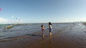Two girls having fun staying on the beach during hot summer. tracking shot. Sariaya, Quezon, Philippines - April 16, 2018: Two girls having fun staying on the stock video