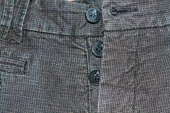 Sarja de Nimes suja em um quadrado com botões Obscuridade do vintage - calças de brim cinzentas, boas para o fundo Fotografia de Stock Royalty Free
