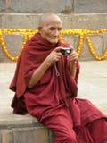 Sarnath, Uttar Pradesh, Indien - 1. November 2009 ein alter buddhistischer Mönch mit der rote Farbrobe, die mit einer Kamera sitz Lizenzfreie Stockfotos