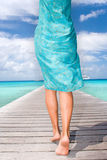 Sarong breeze. Woman in light blue sarong waling on pier Stock Photo