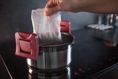 Sarrasin dans des sacs de partie pour la cuisson Faisant cuire le gruau de sarrasin, une femme met un sac pour faire cuire dans u image stock
