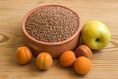 Sarrasin dans une cuvette en céramique à côté de la pomme et des abricots sur l'OE photos stock