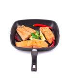 Sartén de tres filetes de color salmón y de pimientas rojas Foto de archivo