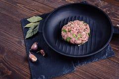 Sartén del arrabio con una Patty hecha de la carne picadita con las hierbas en la piedra y el fondo de madera Imágenes de archivo libres de regalías