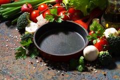 sartén vacía y verduras orgánicas frescas, primer del arrabio  foto de archivo libre de regalías