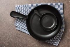 Sartenes grandes y pequeños en la tabla de cocina Imagen de archivo libre de regalías