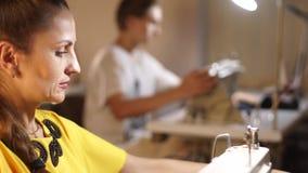 Sarto da donna che lavora ad una macchina per cucire nello studio del sarto alla tavola Occupazione professionale della cucitrice stock footage