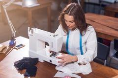 Sarto da donna femminile che lavora con la macchina per cucire, tessuto di cucitura che si siede alla tavola in studio Fotografia Stock Libera da Diritti