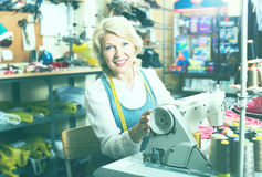 Sarto maturo positivo della donna che usando macchina per cucire Immagine Stock