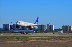 SAS Scandanavian Airlines Passenger Aircraft Landing At Alicante Airport. The flight passes another SAS plane before touching down on the runway Stock Photo