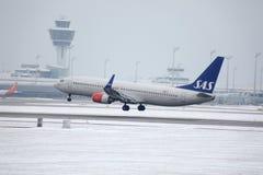 SAS skandinaviska flygbolag Boeing 737-800 LN-RRJ i den Munich flygplatsen, snö Royaltyfri Bild