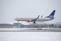SAS skandinaviska flygbolag Boeing 737-800 LN-RRJ i den Munich flygplatsen, snö Royaltyfri Fotografi