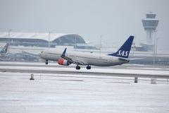 SAS skandinaviska flygbolag Boeing 737-800 LN-RRJ i den Munich flygplatsen, snö Royaltyfria Bilder