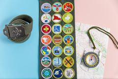 Sash map and compass on blue and pink. SAINT LOUIS, UNITED STATES - MAY 3, 2018:  Boy Scouts of America BSA merit badge sash, belt, compass, and map on pink and Royalty Free Stock Images
