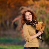 Sasha. red haired woman in beige sweater and colored scarf with stock image