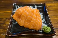 Sashimi σολομών σε ένα μαύρο κεραμικό πιάτο με τη μερίδα Wasabi Στοκ φωτογραφίες με δικαίωμα ελεύθερης χρήσης