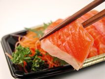 Sashimi and chopsticks. Close up of two chopsticks holding a piece of raw salmon meat.Focus on the chopsticks Stock Photography
