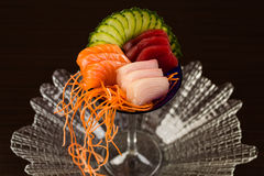Sashimi Cocktail. Assorted fancy sashimi served in a martini glass in a clear glass plate garnished with sliced cucumbers and carrot Royalty Free Stock Images