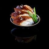 Sashimi con la anguila en una placa negra En un fondo negro con re Fotos de archivo