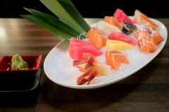 Sashimi cortado misturado dos peixes no gelo na bacia branca Sashimi Salmon Tuna Hamachi Prawn e grupo da calma da ressaca, peixe imagens de stock royalty free