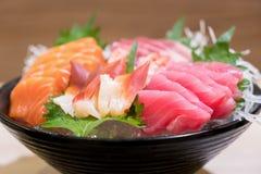 Sashimi cortado misturado dos peixes no gelo na bacia preta Sashimi Salmon Tuna Hamachi Prawn e grupo da calma da ressaca, peixe  fotos de stock royalty free