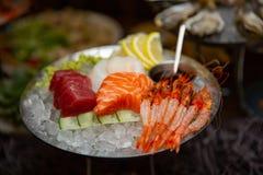 Sashimi cortado misturado dos peixes no gelo na bacia preta Sashimi Salmon Tuna Hamachi Prawn e grupo da calma da ressaca, peixe  foto de stock