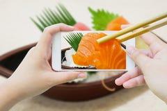 Sashimi di color salmone della tenuta dei bastoncini in telefono cellulare Immagine Stock