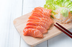 Sashimi di color salmone sul blocco di legno Fotografie Stock