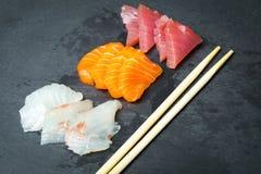 Sashimi frais sur un slatter en pierre noir Crevettes roses de saumons, de thon et sauce à soja Cuisine japonaise traditionnelle Photos libres de droits